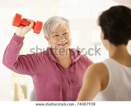 Senior woman doing dumbbell exercise with personal trainer at home, smiling. - stock photo