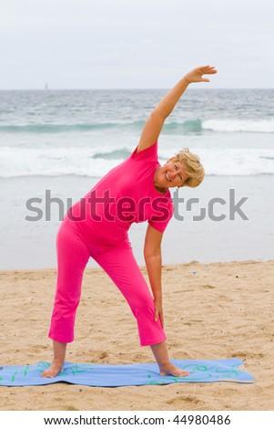 senior woman doing exercise on beach - stock photo