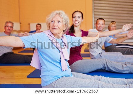 Senior woman doing gymnastics exercises in back training course in gym - stock photo