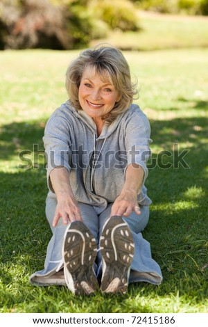 Senior woman doing her streches in the park - stock photo