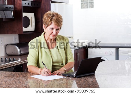 senior woman doing home finance and looks worried - stock photo