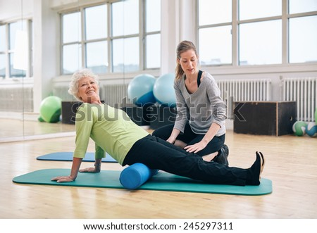 Senior woman doing pilates on the floor with foam roller. Elder woman exercising being assisted by personal trainer at gym. - stock photo
