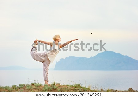 Senior woman doing yoga exercises with mountain on the background - stock photo