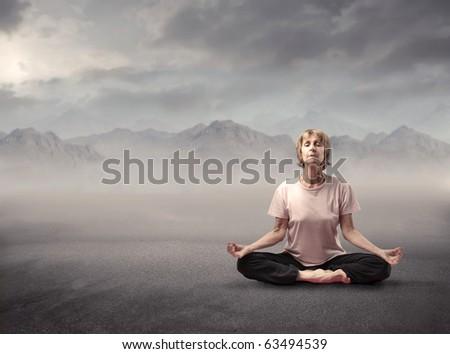 Senior woman doing yoga exercises with mountain on the background - stock photo
