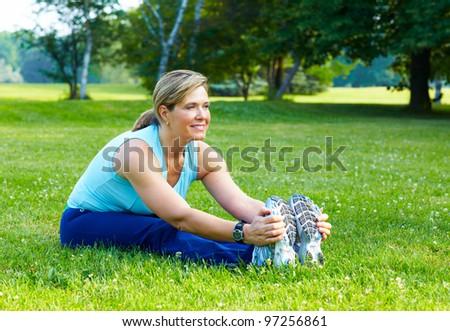 Senior woman doing yoga in the park. Health. - stock photo
