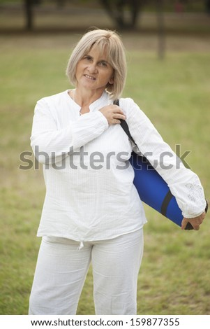 senior woman dressed in white carrying yoga mat in nature - stock photo