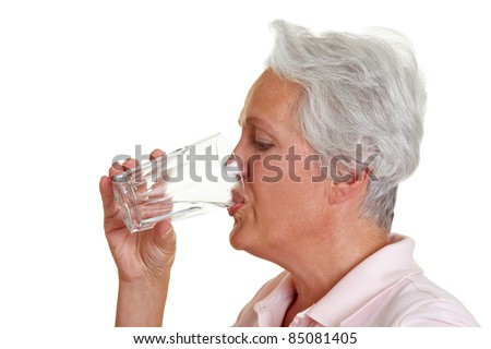 Senior woman drinking a glass of fresh water - stock photo