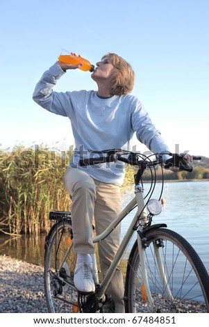 Senior woman drinking an energy drink on a bicycle with lake on the background - stock photo