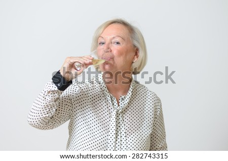 Senior woman drinking champagne looking to the camera with a happy smile as she celebrates a special event