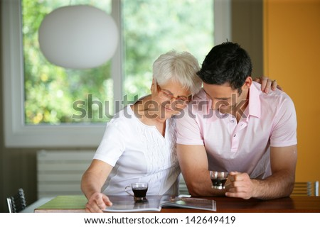 Senior woman drinking coffee with her son - stock photo