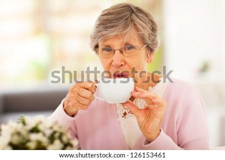senior woman drinking tea at home - stock photo