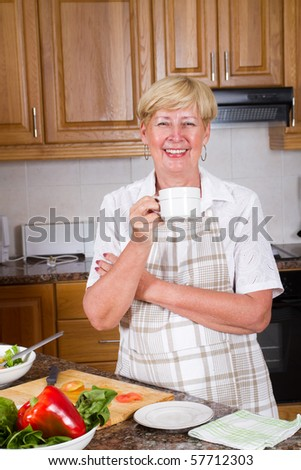 senior woman drinking tea or coffee in kitchen