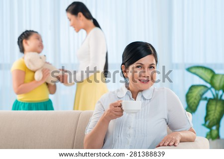 Senior woman drinking tea while her daughter and granddaughter talking in background - stock photo
