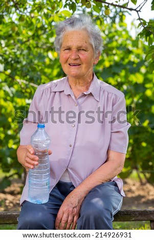 Senior woman drinking water in the orchard - stock photo