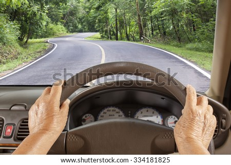 Senior woman driving a car slowly on highway - stock photo