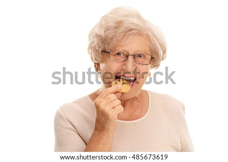 Senior woman eating a cookie isolated on white background