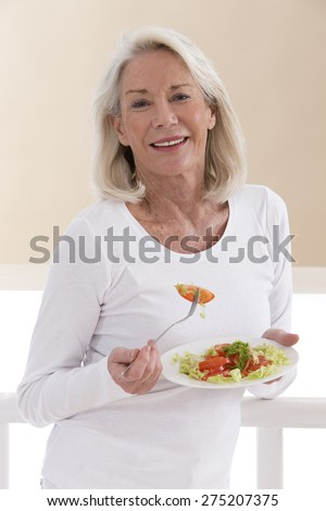 Senior woman eating a healthy salad at the kitchen - stock photo