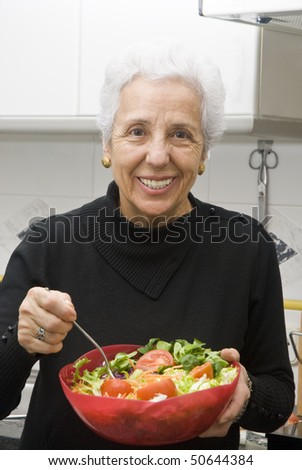 Senior woman eating a healthy salad at the kitchen - stock photo
