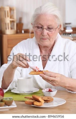 senior woman eating breakfast - stock photo