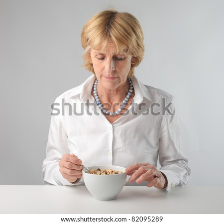 Senior woman eating cereals for breakfast - stock photo