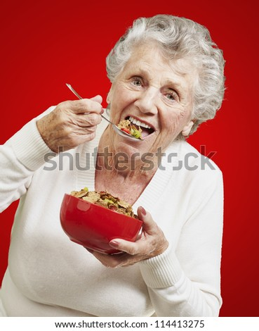 senior woman eating cereals out of a red bowl against a red background