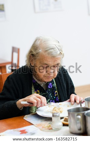 senior woman eating her lunch at home - stock photo