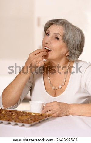 Senior woman eats chocolate candies at home - stock photo