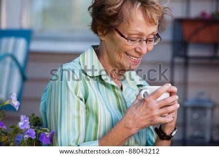 Senior woman enjoying a warm drink in back yard - stock photo