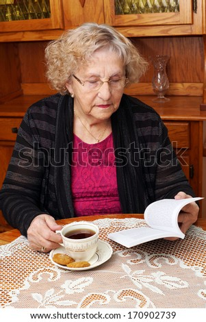 Senior woman enjoying afternoon tea and reading a book at home - stock photo
