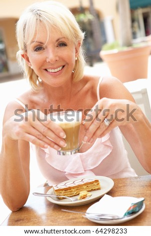 Senior Woman Enjoying Coffee And Cake In Cafe