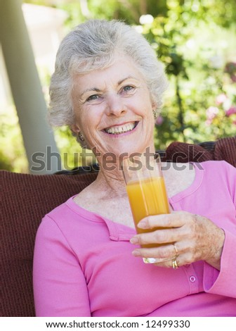 Senior woman enjoying glass of juice sitting on garden seat - stock photo
