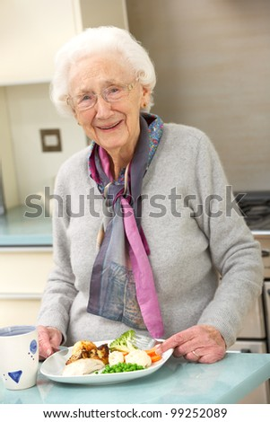 Senior woman enjoying meal in kitchen - stock photo