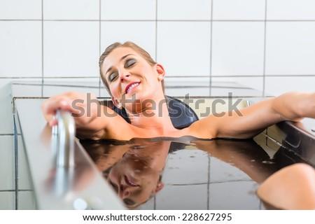 Senior woman enjoying mud bath alternative therapy - stock photo