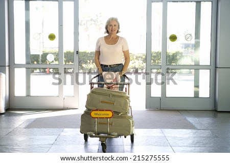 Senior woman entering airport through automatic doors, pushing luggage trolley, smiling, front view, portrait - stock photo