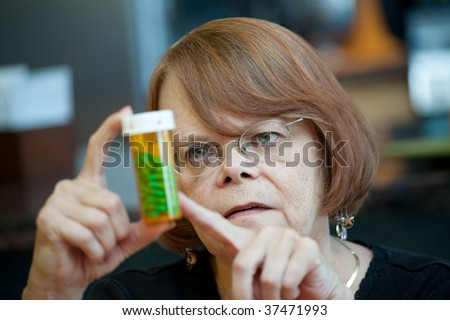 Senior woman examining prescription bottle with green capsules - stock photo