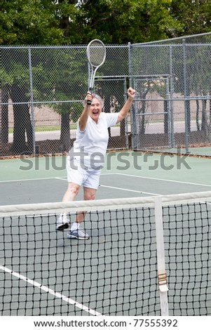 Senior woman excited about winning a tennis match. - stock photo