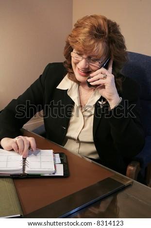 Senior Woman Executive Talking on Phone with agenda - stock photo