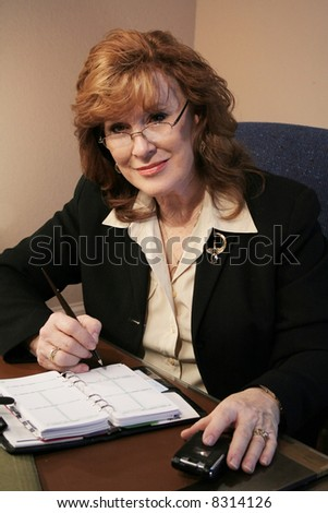 Senior woman executive with schedule and cell phone - stock photo