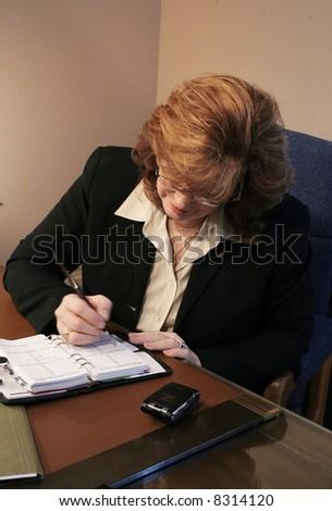 Senior Woman Executive writing in agenda - stock photo