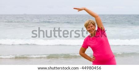 senior woman exercise on beach, - stock photo
