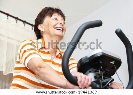 Senior woman exercise on spinning bicycle at home - stock photo