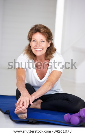 Senior woman exercising at home - stock photo