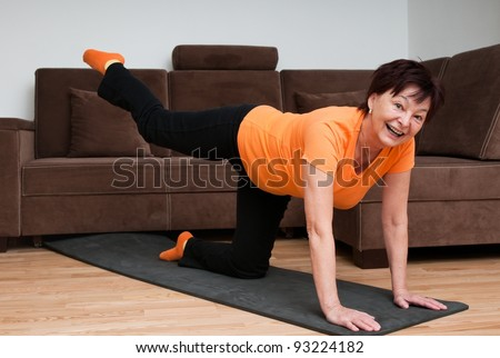 Senior woman exercising at home - stock photo
