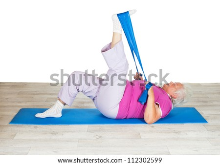 Senior woman exercising for mobility lying on a mat raising her leg in the air using a strap for leverage to improve mobility in her hip - stock photo