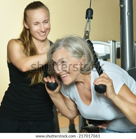 Senior woman exercising in gym with sport coach - stock photo