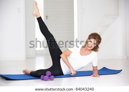 Senior woman exercising in home gym - stock photo