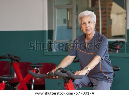 Senior woman exercising on a spinning bicycle - stock photo