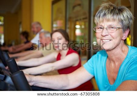 Senior woman exercising on bike in gym - stock photo
