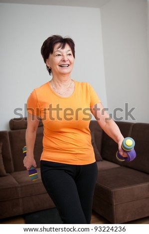 Senior woman exercising with barbells - stock photo