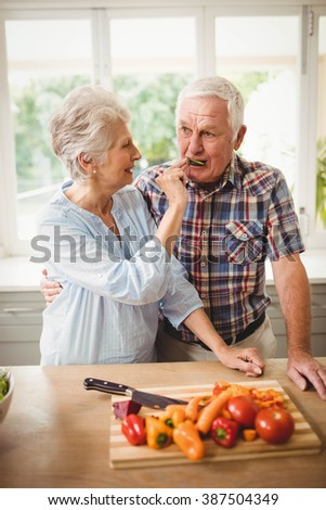 Senior woman feeding a cucumber slice to senior man - stock photo